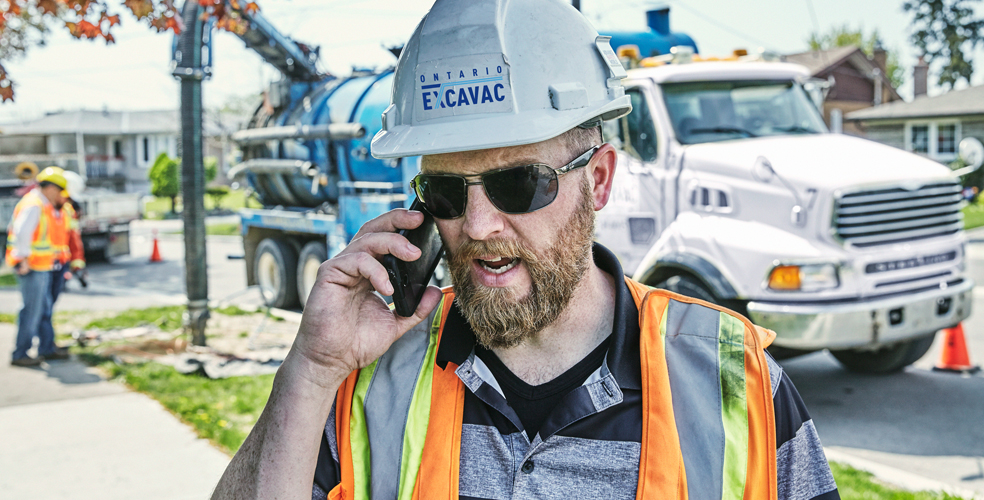photo of employee with hardhat on talking on a cellphone