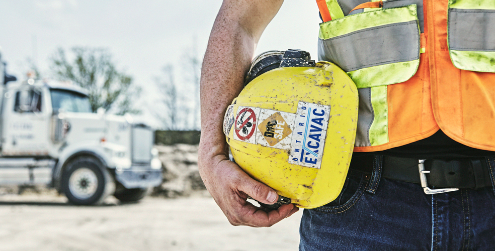 photo of man holding hardhat on against his hip