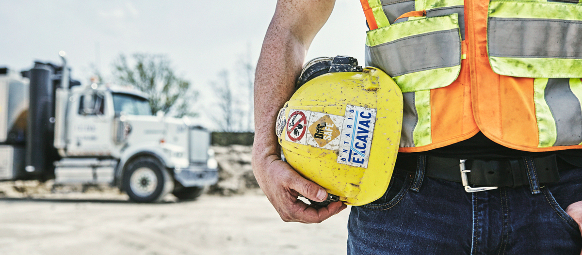 photo of employee holding a hardhat on his hip
