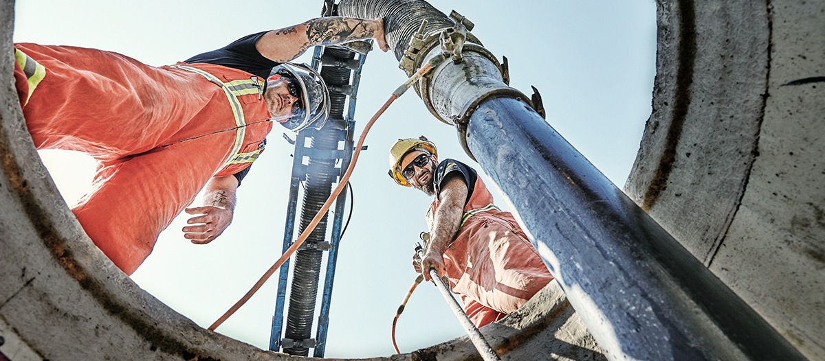 photo of workers holding a vacuum pipe down a hole