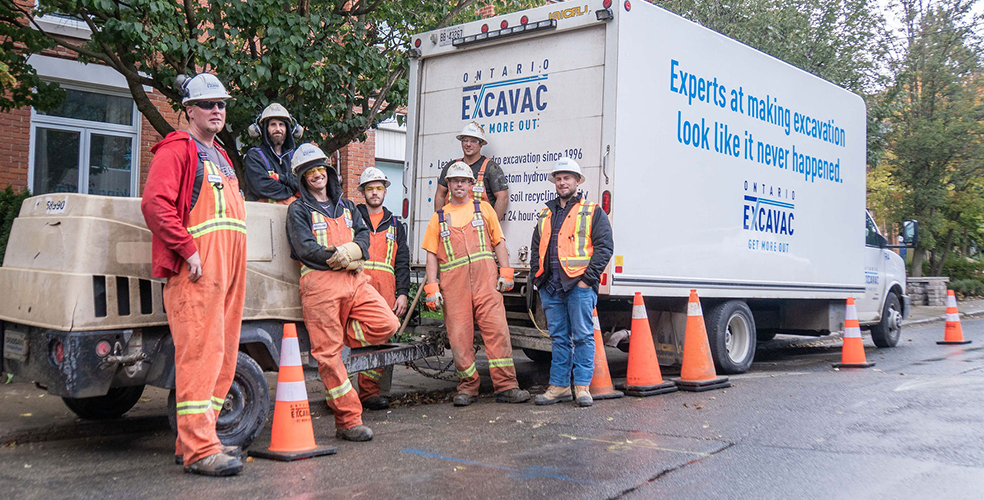 Ontario Excavac employees standing in front of their vehicles