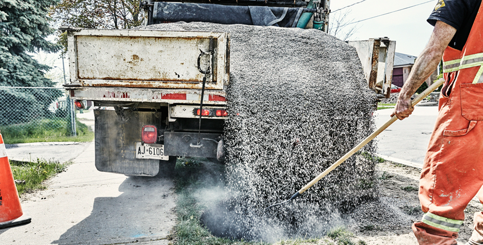 dump truck filling hole with gravel